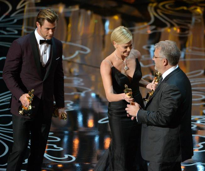 "Presenters Chris Hemsworth, left, and Charlize Theron, center, present Skip Lievsay with the award for best sound mixing for ""Gravity"" during the Oscars at the Dolby Theatre on Sunday, March 2, 2014, in Los Angeles.  (Photo by John Shearer/Invision/AP)"