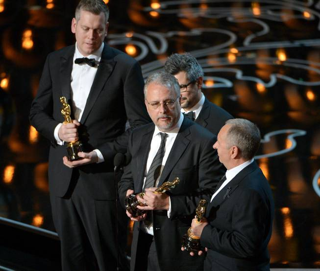 "Christopher Benstead, Niv Adiri, Skip Lievsay, and Chris Munro accept the award for best sound mixing for ""Gravity"" during the Oscars at the Dolby Theatre on Sunday, March 2, 2014, in Los Angeles.  (Photo by John Shearer/Invision/AP)"
