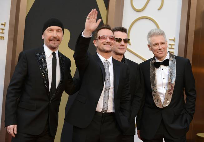 The Edge, from left, Bono, Larry Mullen, Jr., and Adam Clayton of U2 arrive at the Oscars on Sunday, March 2, 2014, at the Dolby Theatre in Los Angeles.  (Photo by Jordan Strauss/Invision/AP)