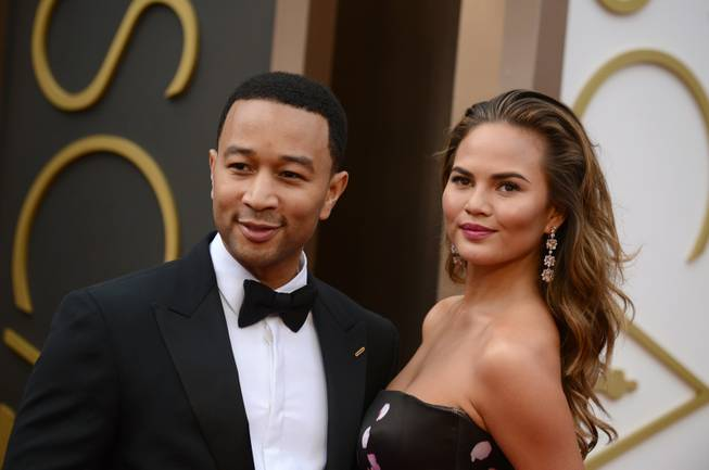 John Legend and Chrissy Teigen arrive at the Oscars on Sunday, March 2, 2014, at the Dolby Theater in Los Angeles.