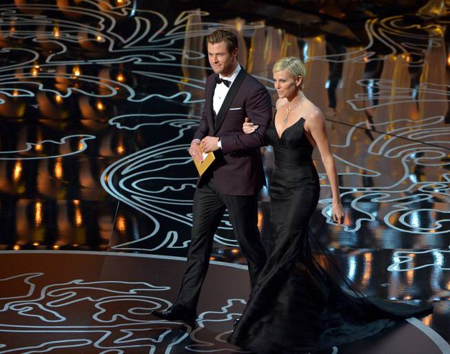 Chris Hemsworth, left, and Charlize Theron walk on stage during the Oscars at the Dolby Theatre on Sunday, March 2, 2014, in Los Angeles.  (Photo by John Shearer/Invision/AP)
