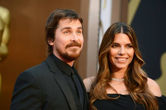Christian Bale, left, and Sibi Blazic arrive at the Oscars on Sunday, March 2, 2014, at the Dolby Theatre in Los Angeles.  (Photo by Jordan Strauss/Invision/AP)