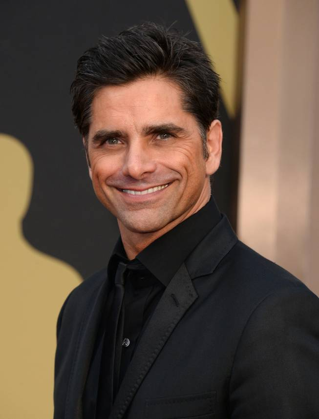 John Stamos arrives at the Oscars on Sunday, March 2, 2014, at the Dolby Theatre in Los Angeles.  (Photo by Jordan Strauss/Invision/AP)