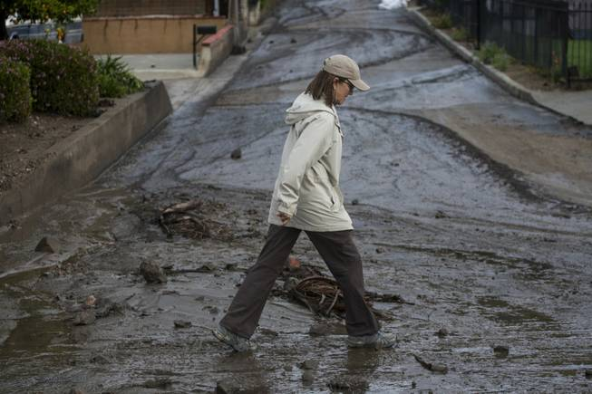 A woman walks over the mud and debris at the corner of Sierra Madre Avenue and Highcrest Road along the hillside in Glendora, Calif. on Saturday, March 1, 2014. A burst of heavy showers before dawn Saturday impacted wildfire-scarred mountainsides above foothill suburbs east of Los Angeles, causing another round of mud and debris flows in the city of Glendora.