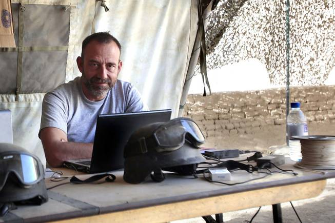 "In this photo released by Spanish newspaper El Periodico de Catalunya on Sunday, March 2, 2014, journalist Marc Marginedas, who works for the newspaper, sits by his laptop at the Canadian base in Nakhonay, Afganistan, in this photo taken on Oct. 10, 2010. Marginedas, who was kidnapped by al-Qaida-linked militants in Syria crossed the border into Turkey on Sunday, March 2, 2014, his newspaper reported, as activists said government airstrikes killed at least 13 people in a northwestern border town. Veteran war correspondent Marginedas was abducted on Sept. 4 near Hama by jihadists belonging to the Islamic State of Iraq and the Levant, a breakaway al-Qaida group. He was ""moved repeatedly"" while in captivity and was accused of spying for the West before his release, his newspaper El Periodico said."
