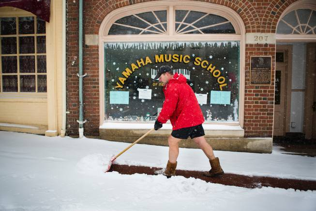 Owner of Bodywork Wayne Gootee shovels the walkway in front of businesses in Fredericksburg, Va during the snowstorm on Monday, March 3, 2014.