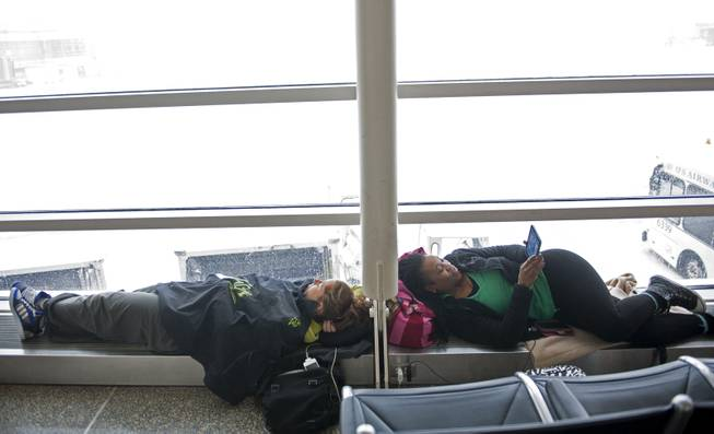 Hedwige Hattab, 29, Grenoble, France, left, and J'Que Ellis, 38, of Huntsville, Ala. wait  for flights to resume at Washington's Ronald Reagan National Airport, Monday, March 3, 2014.