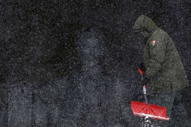 National Park Service employee Eric Tolliver shovels snow and ice at the Lincoln Memorial as snow falls in Washington, Monday, March 3, 2014.