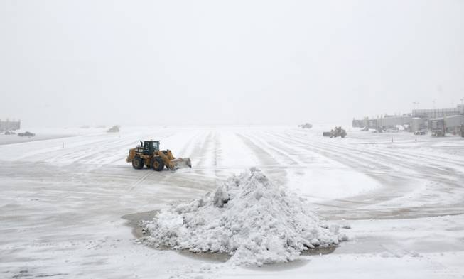 Workers clear the tarmac of snow so that flights can resume at Washington's Ronald Reagan National Airport, Monday, March 3, 2014.