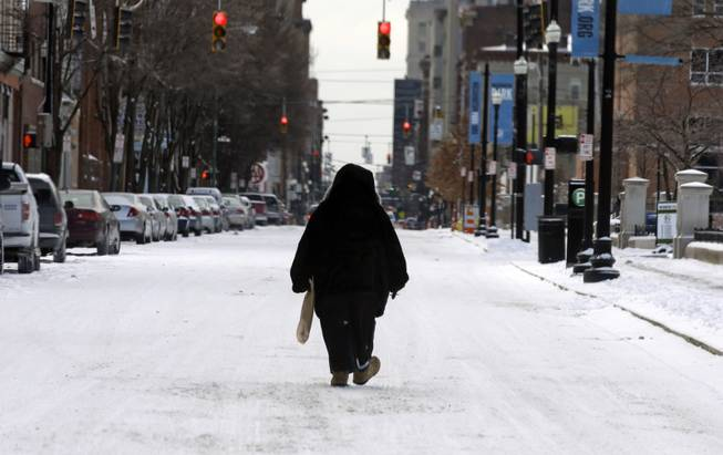A pedestrian walks in the middle of a snow covered street, Monday, March 3, 2014, in downtown Cincinnati. The area received from three to six inches of new snow.