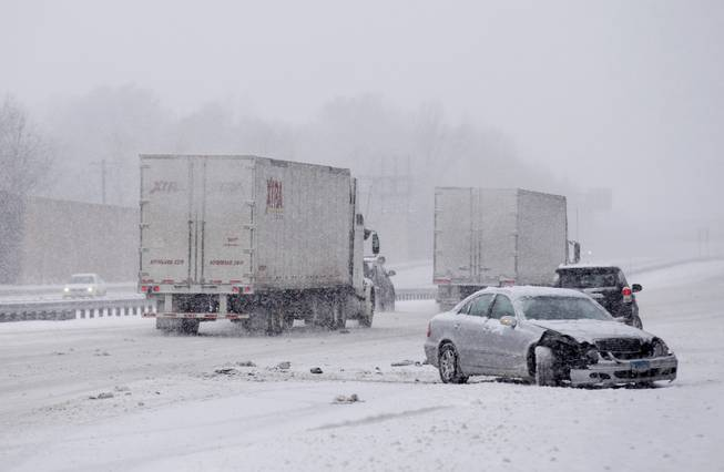A car involved in a crash while traveling on Maryland Route 50 is passed by trucks during a snow storm, Monday, March 3, 2014, in Bowie, Md.