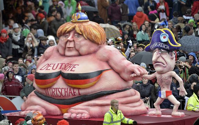 A carnival float caricating German chancellor Angela Merkel, left,  representing  the growing German economy, and a slim French president Francois Hollande during the traditional carnival parade in Duesseldorf, western Germany, on Monday, March 3, 2014. The foolish street spectacles in the carnival centers of Duesseldorf, Mainz and Cologne, watched by hundreds of thousands of people, are the highlights in Germany's carnival season on Rose Monday.  Words at left read: German Economy.