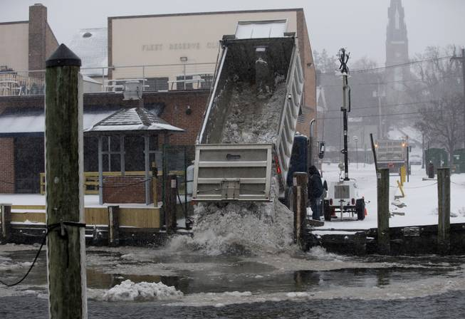 Workers with the City of Annapolis dump snow into Annapolis Harbor as snow continues to fall, Monday, March 3, 2014, in Annapolis, Md.