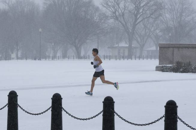 An unidentified man braves the elements as he runs on the National Mall as snow falls in Washington, Monday, March 3, 2014.