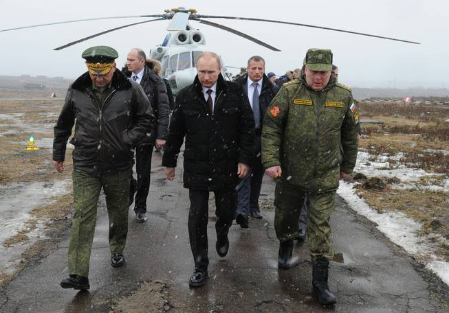 Russian President Vladimir Putin, center, and Defense Minister Sergei Shoigu, left, and the commander of the Western Military District Anatoly Sidorov, right, walk upon arrival to watch military exercise near St. Petersburg, Russia, Monday, March 3, 2014.