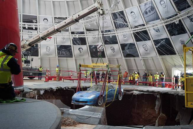 One of eight Chevrolet Corvettes is removed from a sinkhole in the Skydome at the National Corvette Museum on Monday, March. 3, 2014, in Bowling Green, Ky.
