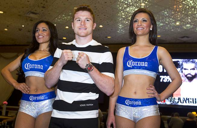 Light middleweight boxer Canelo Alvarez of Mexico poses with Corona Girls in the MGM Grand lobby Tuesday, March 4, 2014. Alvarez will face Alfredo Angulo, also of Mexico, in a non-title, 12-round fight at the MGM Grand Garden Arena on Saturday.