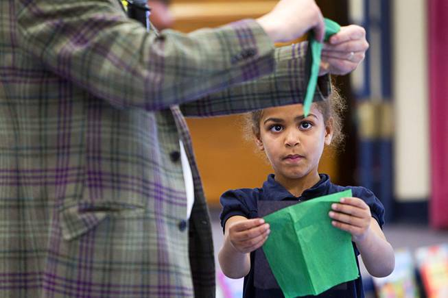 Kindergartener Dariah Tubbs tries to copy comedy-magician Mac King as he makes an origami hat during his Magical Literacy Tour: Nevada Reading Week 2014 with students at Vegas Verdes Elementary School Tuesday, March 4, 2014. For the fourth year, the Harrahs headliner will visit schools to perform magic tricks, talk about the importance of reading and distribute books collected during book drives.