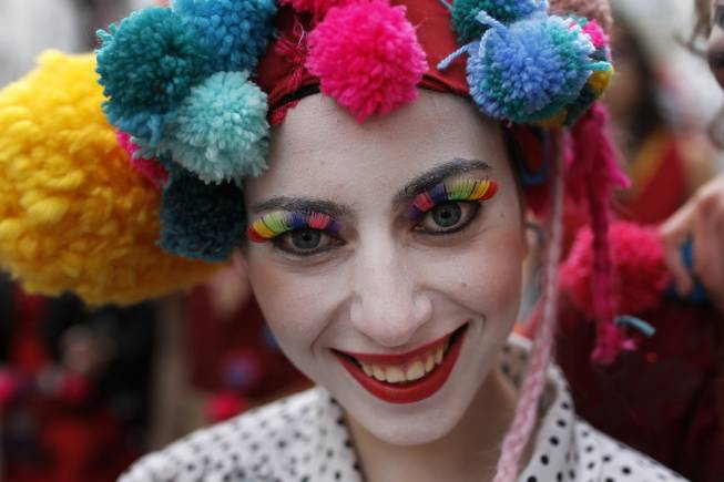 A woman poses for a photograph as she takes part of a Carnival parade in downtown Lisbon, Tuesday, March 4, 2014.