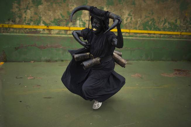 A woman, covered in oil and soot carrying bull horns on his head and cowbells on a belt representing the devil, runs while participating in carnival celebrations in the small village of Luzon, Spain, Saturday, March 1, 2014. Preserved records from the 14th century document Luzon's carnival, but the real origin of the tradition could be much older. Carnival festivals are celebrated in their own way around hundreds of villages in Spain.
