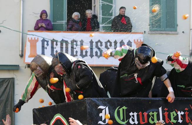 People wearing protection helmets and costumes throw oranges as part of Carnival celebrations in the northern Italian Piedmont town of Ivrea, Tuesday, March 4, 2014. The traditional orange throwing battle has its roots in the middle of the XIXth century.