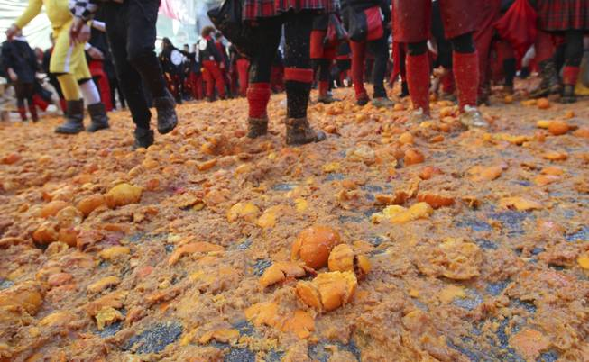 People walk over smashed oranges covering the ground during an oranges battle part of Carnival celebrations in the northern Italian Piedmont town of Ivrea, Tuesday, March 4, 2014. The traditional orange throwing battle has its roots in the middle of the XIXth century.