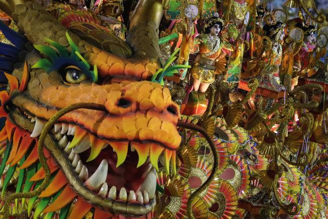 Performers from the Beija Flor samba school parade on a float during carnival celebrations at the Sambadrome in Rio de Janeiro, Brazil, Monday, March 3, 2014.
