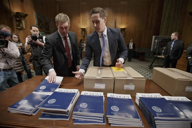 Copies of President Barack Obama's proposed fiscal 2015 budget are set out for distribution by Senate Budget Committee Clerk Adam Kamp, center, on Capitol Hill in Washington, Tuesday, March 4, 2014.