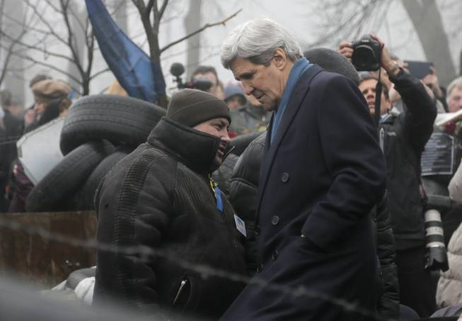 U.S. Secretary of State John Kerry, right, inspects protesters barricades in Kiev, Ukraine, Tuesday, March, 4, 2014. In a somber show of U.S. support for Ukraine'€™s new leadership, Kerry walked the streets Tuesday where nearly 100 anti-government protesters were gunned down by police last month, and promised beseeching crowds that American aid is on the way. The Obama administration announced a $1 billion energy subsidy package in Washington as Kerry was arriving in Kiev.
