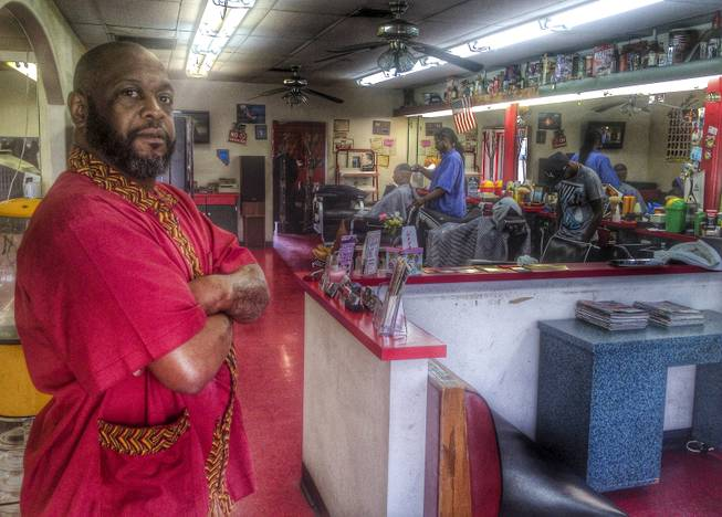 Michael Jones, left, co-owner of A Cut Above The Rest barbershop, located at Carson Avenue and 7th Street Wednesday, March 5, 2014. Tony Hsieh's Downtown Project has purchased the the barbershop's building but Jones says his business, which has a lease into 2015, is being allowed to stay.