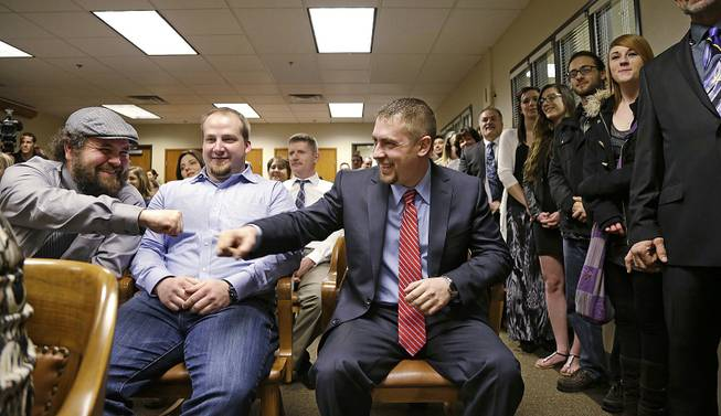 Sean Green, seated right, is congratulated by Sean Fitzgerald, left, as Scott O'neil looks on before Green is issued his new Washington state legal marijuana license Wednesday, March 5, 2014, in Olympia, Wash.