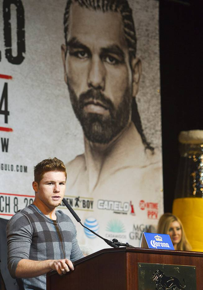 Super welterweight boxer Canelo Alvarez speaks during a news conference at the MGM Grand Thursday, March 6, 2014. Alvarez and Alfredo Angulo, both of Mexico, will fight at the MGM Grand Garden Arena on Saturday. An image of Angulo is shown on a banner behind Alvarez.