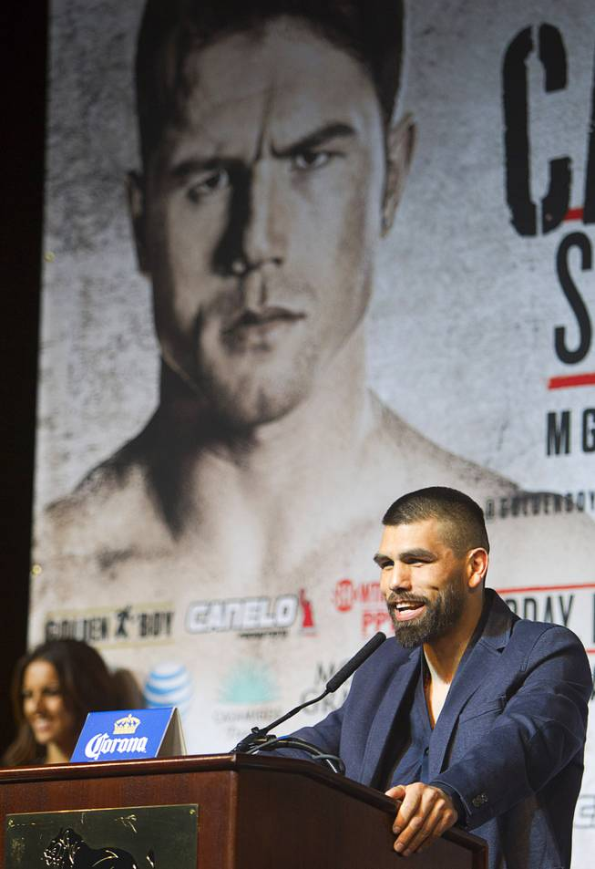 Super welterweight boxer Alfredo Angulo speaks during a news conference at the MGM Grand Thursday, March 6, 2014. Angulo and Canelo Alvarez, both of Mexico, will fight at the MGM Grand Garden Arena on Saturday. An image of Alvarez is shown on a banner behind Angulo.