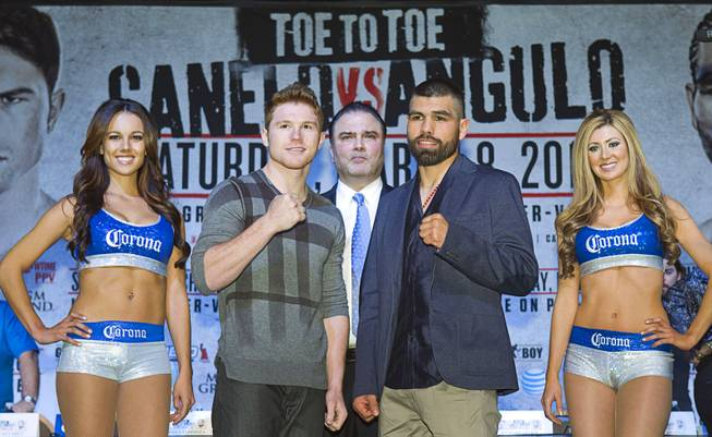 Super welterweight boxers Canelo Alvarez, left, and Alfredo Angulo face off during a news conference at the MGM Grand Thursday, March 6, 2014. Richard Schaefer, CEO of Golden Boy Promotions, looks on at center. Alvarez and Angulo, both of Mexico, will fight at the MGM Grand Garden Arena on Saturday.