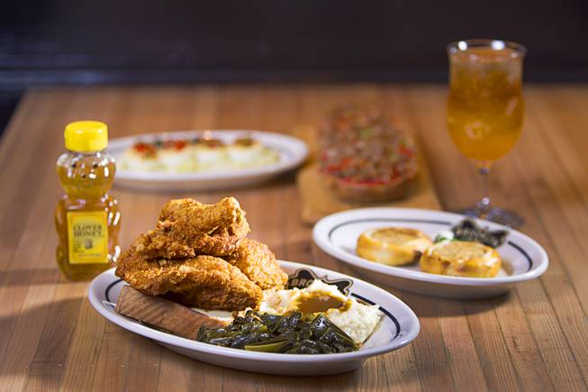 A Fried Chicken Dinner served with bread, honey, collard greens and mashed potatoes at the Brooklyn Bowl in the Linq Thursday, March 6, 2014. Also pictured are Egg Shooters, Potato and Onion Knish and San Gennaro Pizza.