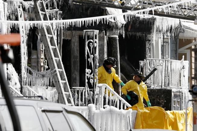 Officials exit from a home where a fire broke out early in the morning on Thursday, March 6, 2014, in Jersey City, N.J.