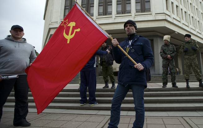 Local residents hold a Soviet flag as members of Cossack militia guard the local parliament building in Simferopol, Ukraine, on Thursday, March 6, 2014. Lawmakers in Crimea declared their intention Thursday to split from Ukraine and join Russia instead, and scheduled a referendum in 10 days for voters to decide the fate of the disputed peninsula. Russia's parliament, clearly savoring the action, introduced a bill intended to make this happen.