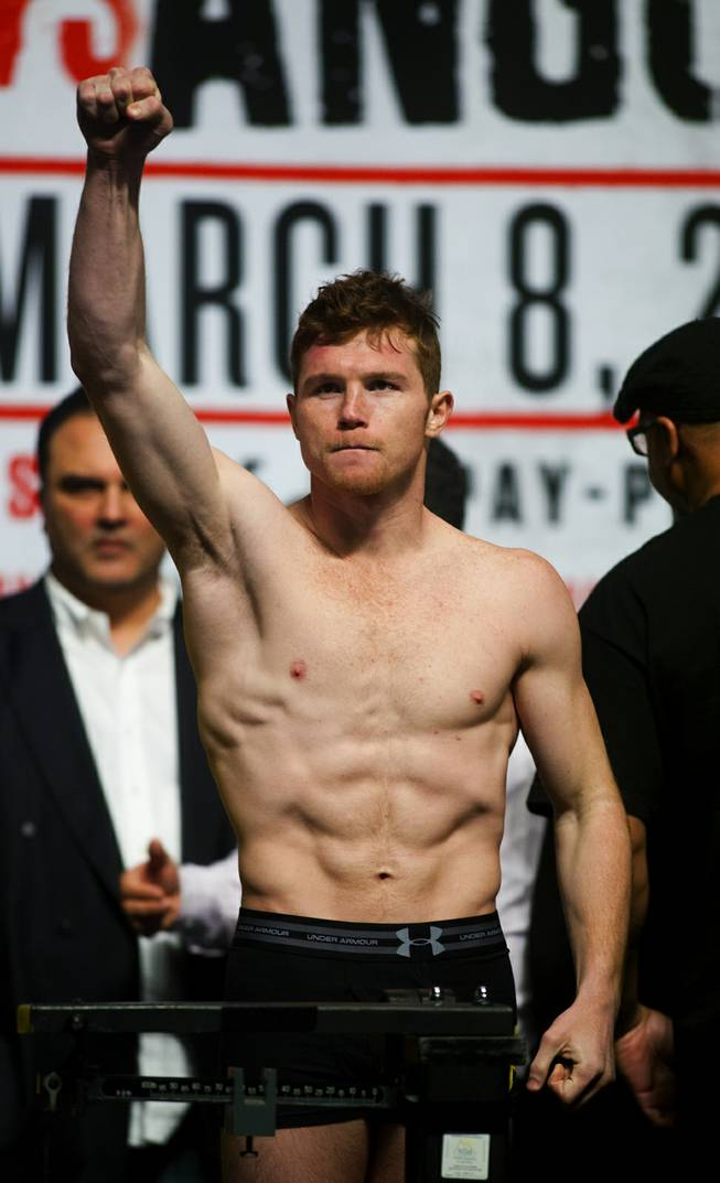 Super welterweight Canelo Alvarez of Mexico pumps his fist to the fans on hand for his weigh-in at the MGM Grand Arena on Friday, March 07, 2014.
