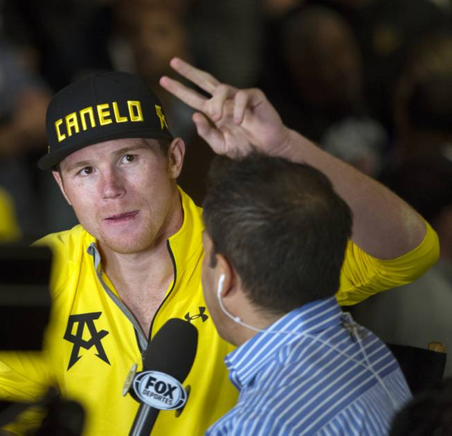 Super welterweight Canelo Alvarez of Mexico signals fans during an interview following his weigh-in at the MGM Grand Arena on Friday, March 07, 2014.