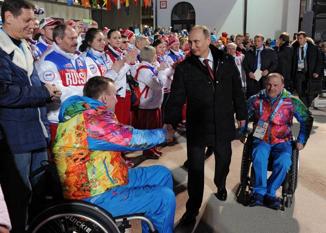 In this photo taken Thursday, March 6, 2014, Russian President Vladimir Putin, center, greets athletes during his visit to the mountain Paralympic village in Krasnaya Polyana, Russia, on the eve of the opening ceremony of the 2014 Winter Paralympics in Sochi. At right is Sergei Shilov, six time Paralympic Champion.
