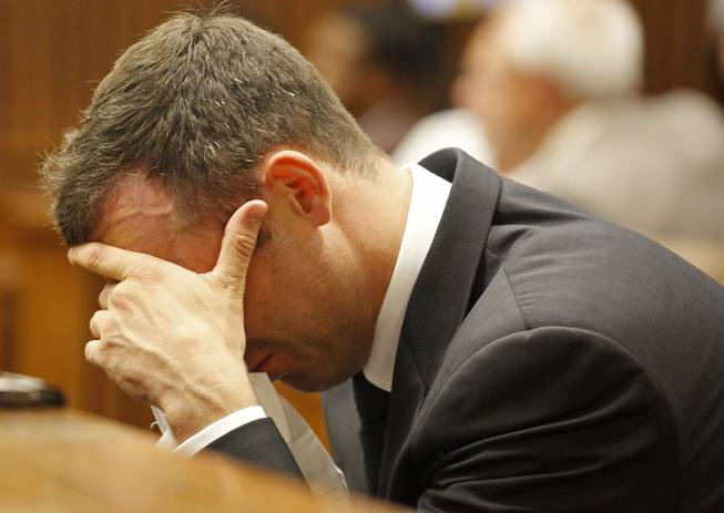Oscar Pistorius puts his hand to his face as he listens to cross questioning about the events surrounding the shooting death of his girlfriend Reeva Steenkamp, in court during his trial in Pretoria, South Africa, Friday, March 7, 2014.