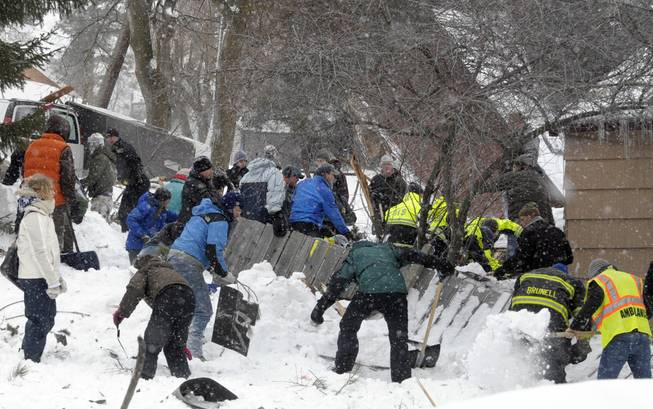 Rescuers dig frantically at the scene of an avalanche in Missoula's Rattlesnake Valley on Friday, Feb. 28, 2014, looking for a boy buried in the snow.