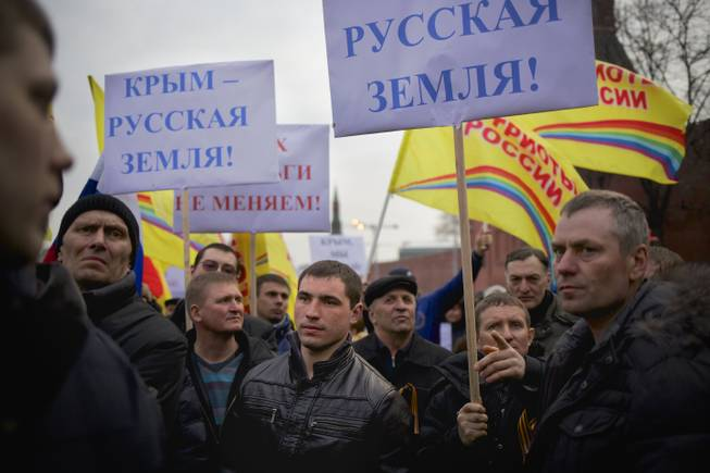 "Pro-Putin demonstrators hold posters reading ""Crimea is Russian land!"" as they gather towards to Red Square in Moscow, Russia, Friday, March 7, 2014."