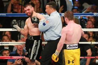 Referee Tony Weeks pushes Alfredo Angulo away from Saul