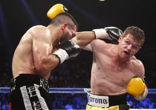 Alfredo Angulo, left, battles it out with Canelo Alvarez, both of Mexico, during their super welterweight fight at the MGM Grand Garden Arena on Saturday, March 8, 2014.