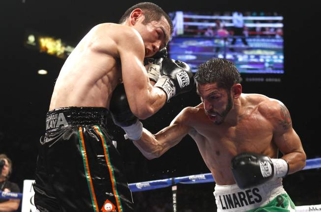 Nihito Arakawa of Japan takes a punch from Jorge Linares of Venezuela during their lightweight fight at the MGM Grand Garden Arena on Saturday, March 8, 2014.