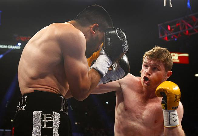 Alfredo Angulo, left, takes a punch from Canelo Alvarez, both of Mexico, during their super welterweight fight at the MGM Grand Garden Arena on Saturday, March 8, 2014.