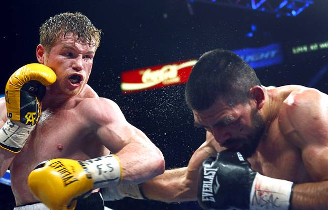 Canelo Alvarez, left, connects on Alfredo Angulo, both of Mexico, during their super welterweight fight at the MGM Grand Garden Arena Saturday, March 8, 2014.