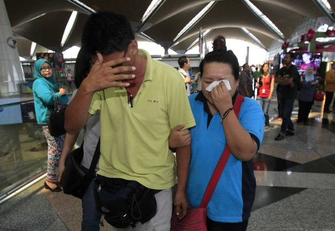 A woman wipes her tears after walking out of the reception center and holding area for family and friends of passengers aboard a missing Malaysia Airlines plane at Kuala Lumpur International Airport in Sepang, Malaysia, on Saturday, March 8, 2014.