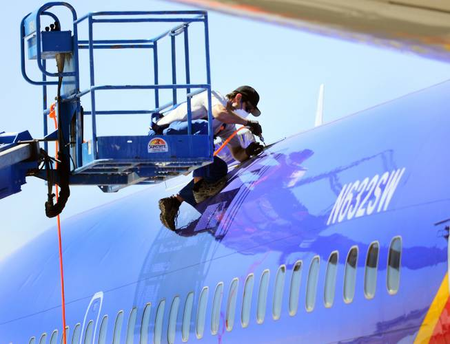 This April 3, 2011, file photo shows a member of the National Transportation Safety Board investigating the emergency landing of Southwest Airlines flight 812 by cutting away a portion of the plane's fuselage in Yuma, Ariz.
